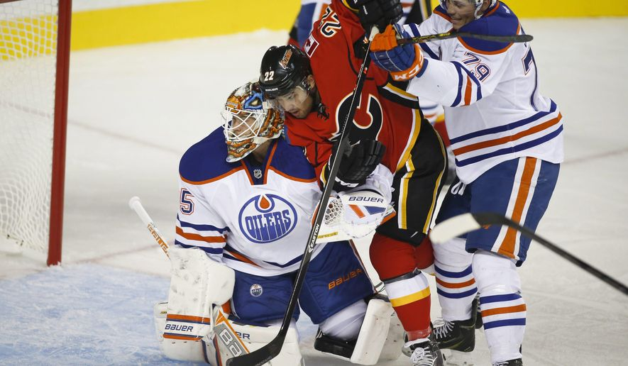 Edmonton Oilers goalie Viktor Fasth, left, has Calgary Flames Devin Setoguchi, center, checked into him by teammate Dillon Simpson during the first period of an NHL preseason hockey game in Calgary, Alberta, Sunday, Sept. 21, 2014. (AP Photo/The Canadian Press, Jeff McIntosh)