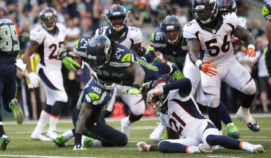 Seattle Seahawks running back Marshawn Lynch dives in for the game-winning touchdown in overtime of an NFL football game against the Denver Broncos, Sunday, Sept. 21, 2014, in Seattle. The Seahawks defeated the Broncos 26-20. (AP Photo/John Froschauer)