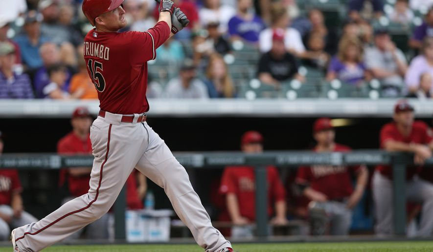 Arizona Diamondbacks' Mark Trumbo follows the flight of his two-run home run against the Colorado Rockies in the sixth inning of the Rockies' 8-3 victory in a baseball game in Denver on Sunday, Sept. 21, 2014. (AP Photo/David Zalubowski)