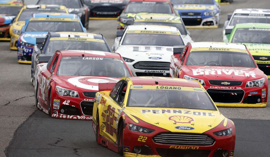 Joey Logano (22) takes the lead on the final restart during the NASCAR Sprint Cup series auto race at New Hampshire Motor Speedway on Sunday, Sept. 21, 2014, in Loudon, N.H. Logano went on to win the race. (AP Photo/Jim Cole)