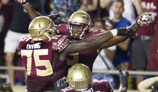 Florida State running back Karlos Williams, top, celebrates his game-winning touchdown in overtime with teammates Cameron Erving, center, and Bobby Hart after an NCAA college football game against Clemson in Tallahassee, Fla., Saturday, Sept. 20, 2014.  Florida State defeated Clemson 23-17 in overtime. (AP Photo/Mark Wallheiser)