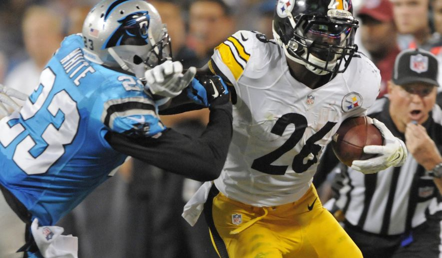 Carolina Panthers' Melvin White (23) tries to tackle Pittsburgh Steelers' Le'Veon Bell (26) during the first half of an NFL football game in Charlotte, N.C., Sunday, Sept. 21, 2014. (AP Photo/Mike McCarn)