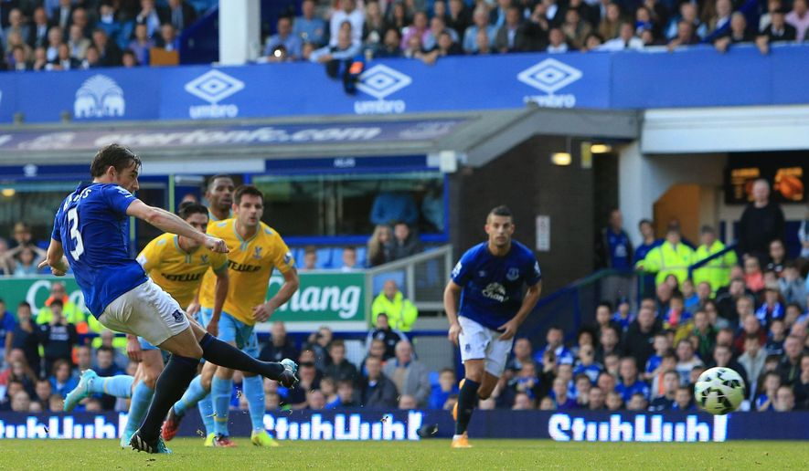 Everton's Leighton Baines, left, scores his side's second goal of the game during their English Premier League soccer match against Crystal Palace at Goodison Park, Liverpool, England, Sunday, Sept. 21, 2014. (AP Photo/Peter Byrne, PA Wire)     UNITED KINGDOM OUT    -   NO SALES    -   NO ARCHIVES