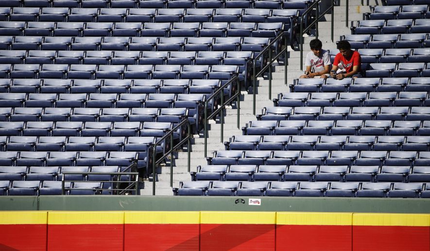 Atlanta Braves fans sits in the outfield stands after the Braves lost to the New York Mets 10-2 in a baseball game, Sunday, Sept. 21, 2014, in Atlanta. (AP Photo/David Goldman)