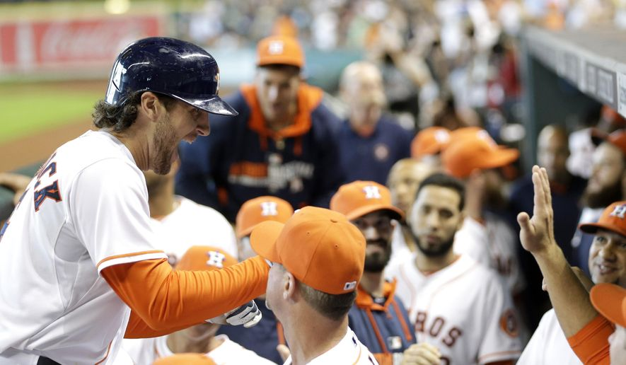 Houston Astros' Jake Marisnick, left, is congratulated as he returns to the dugout after hitting a three-run home run against the Seattle Mariners during the seventh inning of a baseball game, Sunday, Sept. 21, 2014, in Houston. (AP Photo/David J. Phillip)