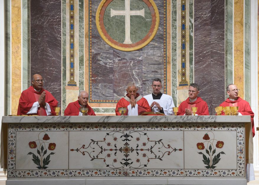 Donald Cardinal Wuerl, Archbishop of Washington, center, prayers over communion during Mass of Thanksgiving in Celebration of the 75th Anniversary of the Archdiocese of Washington at the Cathedral of Saint Matthew The Apostle in Northwest on Sunday, September 21, 2014. Khalid Naji-Allah/ Special to The Washington Times