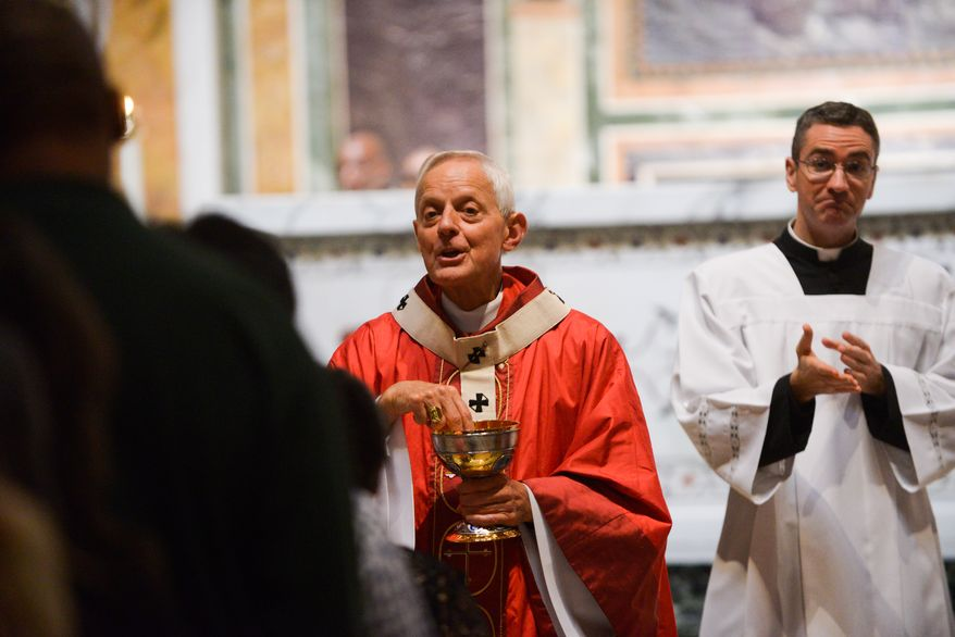 Donald Cardinal Wuerl, Archbishop of Washington, center, prepares to give communion during Mass of Thanksgiving in Celebration of the 75th Anniversary of the Archdiocese of Washington at the Cathedral of Saint Matthew The Apostle in Northwest on Sunday, September 21, 2014. Khalid Naji-Allah/ Special to The Washington Times