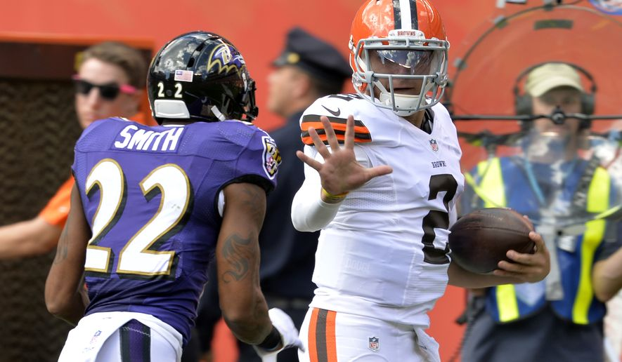 Cleveland Browns quarterback Johnny Manziel (2) runs from Baltimore Ravens cornerback Jimmy Smith after catching a pass in the second quarter of an NFL football game Sunday, Sept. 21, 2014, in Cleveland. The play was called back on a Browns penalty. (AP Photo/David Richard)
