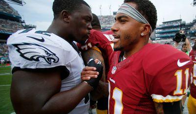 Washington Redskins' DeSean Jackson, right, meets with Philadelphia Eagles' Cedric Thornton before an NFL football game, Sunday, Sept. 21, 2014, in Philadelphia. (AP Photo/Matt Rourke)