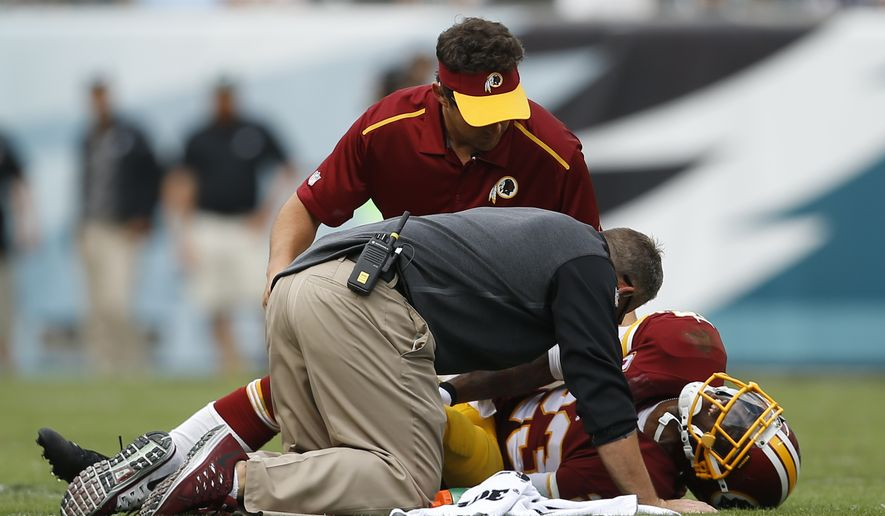 Trainers attend to Washington Redskins cornerback DeAngelo Hall during the second half of an NFL football game against the Philadelphia Eagles, Sunday, Sept. 21, 2014, in Philadelphia. (AP Photo/Michael Perez)