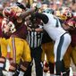 Eagles' Jason Peters, right, and the Redskins' Chris Baker, left, brawl in the fourth quarter as an official tries to break it up during an NFL football game in Philadelphia, Sunday, Sept. 21, 2014. (AP Photo/Philadelphia Daily News, David Maialetti)
