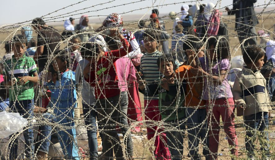 Several hundred Syrian refugees wait to cross into Turkey at the border in Suruc, Turkey, Sunday, Sept. 21, 2014. Turkey opened its border Saturday to allow in up to 60,000 people who massed on the Turkey-Syria border, fleeing the Islamic militants' advance on Kobani.(AP Photo/Burhan Ozbilici)