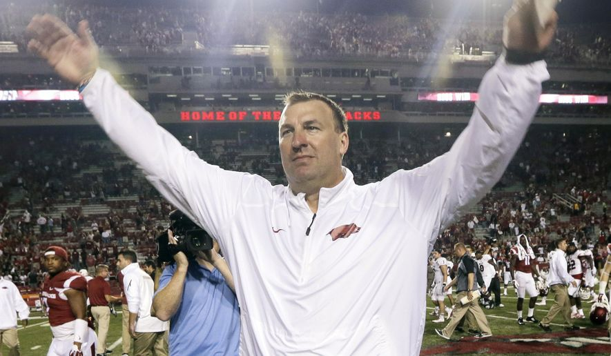 In this photo taken Saturday, Sept. 20, 2014, Arkansas coach Bret Bielema waves after Arkansas defeated Northern Illinois 52-14 in an NCAA college football game in Fayetteville, Ark. The Razorbacks hope to end their 13-game Southeastern Conference losing streak this week when they travel to Arlington, Texas to face No. 6 Texas A&M. (AP Photo/Danny Johnston)