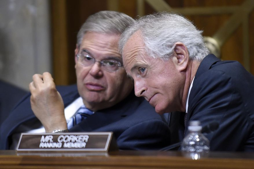 FILE - In this July 29, 2014, file photo, Senate Foreign Relations Committee Chairman Sen. Robert Menendez, left, D-N.J., talks with ranking member Sen. Bob Corker, R-Tenn., on Capitol Hill in Washington. In the Senate Foreign Relations Committee, Menendez and Corker say they'll draft a bill in the lame-duck session repealing what they call outdated authorizations for the use of force and replace them with a new one. (AP Photo/Susan Walsh, File)