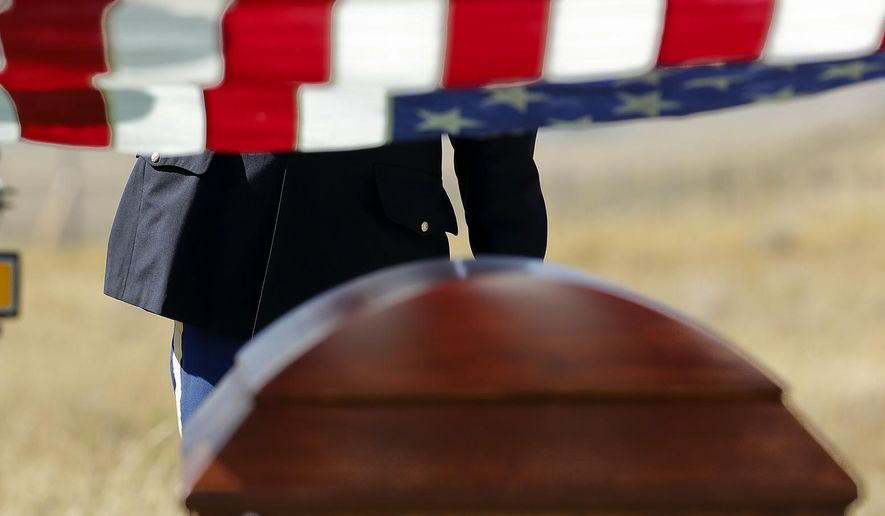Montana Army National Guard chaplain Ken DuVall salutes the casket of William Bernier during a burial ceremony in the Augusta Cemetery with full military honors Friday, Sept. 19, 2014. Bernier was missing since being shot down in a B-24D Liberator over Madang Province, New Guinea, on April 10, 1944, during World War II. (AP Photo/The Great Falls Tribune, Larry Beckner)  NO SALES