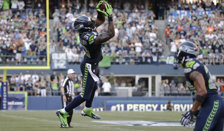 Seattle Seahawks strong safety Kam Chancellor pulls down an interception in the second half of an NFL football game against the Denver Broncos, Sunday, Sept. 21, 2014, in Seattle. (AP Photo/Elaine Thompson)