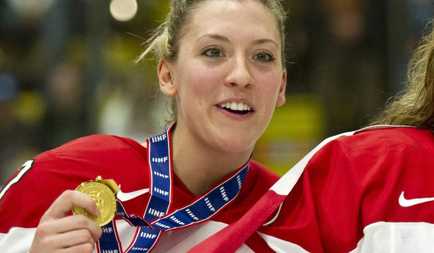 FILE - In this April 14, 2012, file photo, Canada's Meghan Agosta shows off her gold medal after Canada defeated the United States at the World Women's Ice Hockey Championships in Burlington, Vt. When her teammates arrive Monday, Sept. 22, 2014,  in Calgary for training camp, Agosta will instead report to the Justice Institute of British Columbia with her badge and gun. The three-time Olympic gold medallist in women's hockey is training to be a police officer in the city where she earned one of those gold medals.(AP Photo/The Canadian Press, Paul Chiasson, File)