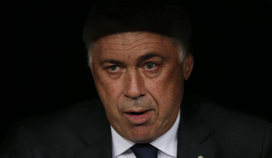 Real Madrid's coach Carlo Ancelotti takes his seat in the dugout before the Champions League Group B soccer match between Real Madrid and Basel at the Santiago Bernabeu stadium in Madrid, Spain, Tuesday Sept. 16, 2014. (AP Photo/Daniel Ochoa de Olza)