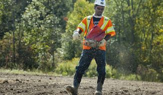 In a Friday, Sept. 19 photo, worker Broderick Curney spreads seed by hand along the Enbridge Pipeline right-of-way in St. Clair Township, Mich. Construction has finished in St. Clair County on part of the Enbridge oil pipeline replacement project. An Enbridge spokesman tells the Times Herald of Port Huron Monday, Sept. 22, 2014, that construction crews will stay in the area to complete land restoration until winter. He says the oil should flow through the replacement line by the end of September.(AP Photo/The Times Herald, Jeffrey M Smith)