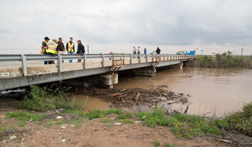 Members of the Pecos fire department, with officials from numbering counties and Federal officials, inspect the rising water level on the Pecos River at the Barstow bridge in Ward County, Texas, Monday, Sept. 22, 2014. (AP Photo/The Odessa American, Courtney Sacco)