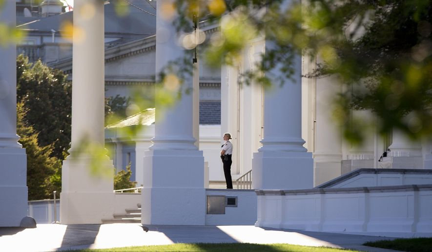 A member of the Secret Service Uniformed Division looks out from the North Portico of the White House in Washington, Monday, Sept. 22, 2014. The Secret Service tightened their guard outside the White House after Friday's embarrassing breach in the security of one of the most closely protected buildings in the world. A man is accused of scaling the White House perimeter fence, running across the lawn and entering the presidential mansion before agents stopped him. (AP Photo/Carolyn Kaster)