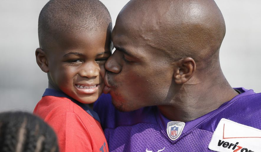 FILE - In this Aug. 1, 2014, file photo, Minnesota Vikings running back Adrian Peterson gives his son Adrian Jr. a kiss following an NFL football training camp practice in Mankato, Minn. By the time the typical player signs an NFL contract, around 100 scouts, coaches and general managers have pored over his history. Very little in the portfolios collected on Ray Rice or Adrian Peterson foreshadowed the issues they're dealing with now. (AP Photo/Charlie Neibergall, File)