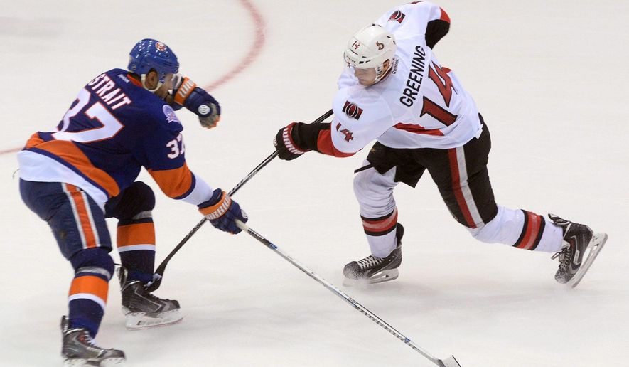 Ottawa Senators Colin Greening takes a shot past N.Y. Islanders Brian Strait during second period pre-season NHL action in St.John's, Newfoundland and Labrador, on Monday, Sept. 22, 2014. (AP Photo/The Canadian Press, Keith Gosse)