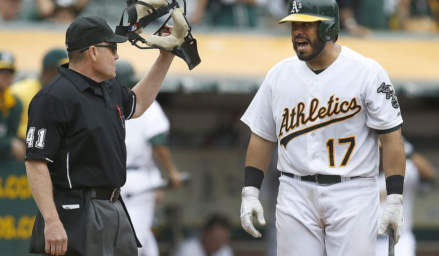 Oakland Athletics' Geovany Soto (17) argues with home plate umpire Jerry Meals, left, after striking out against the Philadelphia Phillies in the ninth inning of a baseball game Sunday, Sept. 21, 2014, in Oakland, Calif. The A's won 8-6 in 10 innings. (AP Photo/Tony Avelar)