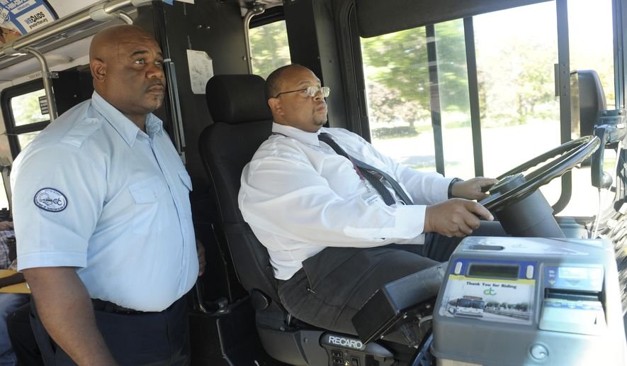 In a Sept. 8, 2014, photo, Jessie Gordon, left, DOT trainer, assists new bus driver James Burse, 46, as he drives through downtown Detroit on his way to his Lafayette Blvd. & Van Dyke route. DDOT is making an attempt to attract more drivers despite the low pay, rigorous requirements and past issues with safety.(AP Photo/Detroit News, Clarence Tabb Jr.)  DETROIT FREE PRESS OUT; HUFFINGTON POST OUT