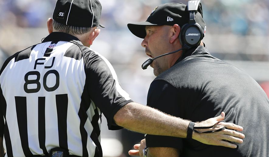 Jacksonville Jaguars head coach Gus Bradley, right, discusses a call with field judge Greg Gautreaux during the first half of an NFL football game against the Indianapolis Colts in Jacksonville, Fla., Sunday, Sept. 21, 2014. (AP Photo/Stephen B. Morton)