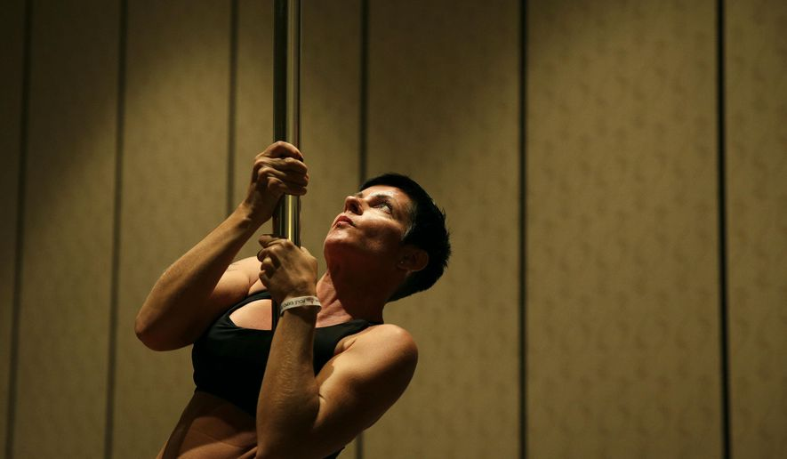In this Sept. 7, 2014 photo, Heidi Nilsson participates in a workshop at the Pole Expo in Las Vegas. Poles have long been a staple of strip clubs, but many of the attendees at the expo are taking the lead of expo founder Fawnia Dietrich and refining their slinky craft as a workout activity. (AP Photo/John Locher)