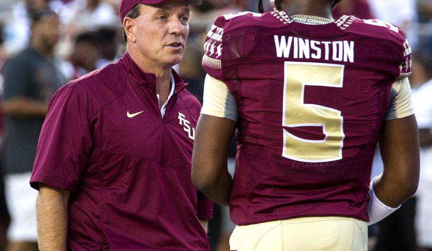 Florida State coach Jimbo Fisher talks to suspended Heisman quarterback Jameis Winston, who dressed in full pads for pre game warm ups, sending him back to the locker room to change before FSU's NCAA college football game against Clemson in Tallahassee, Fla., Saturday, Sept. 20, 2014. Winston rejoined his teammates  in regular clothes. (AP Photo/Mark Wallheiser)