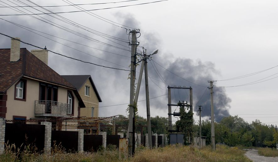 Smoke rises over a residential area in the north of the rebel-held city of Donetsk, eastern Ukraine, Monday, Sept. 22, 2014. A cease-fire was called on Sept. 5 but has been violated repeatedly. Negotiators from Ukraine, Russia, the rebels and the Organization for Security and Cooperation in Europe last week tried to further the peace process with an agreement calling for both sides to halt their advances and for pulling back heavy artillery in order to create a buffer zone. (AP Photo/Darko Vojinovic)