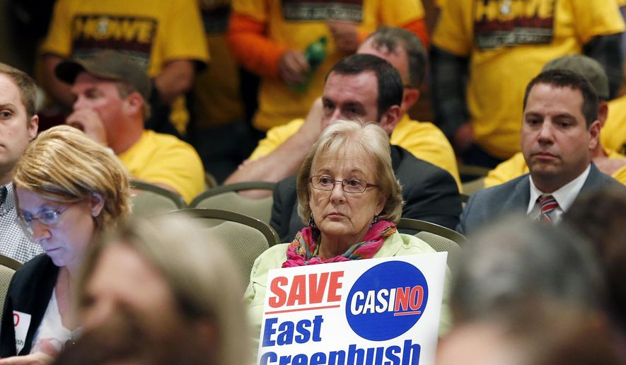 Marie Cookson of East Greenbush, N.Y., holds a sign opposing a casino in her town during a public meeting on casinos on Monday, Sept. 22, 2014, in Albany, N.Y. Supporters and critics of proposals for an Albany area casino are weighing in as three days of public hearings on casinos planned for upstate New York get underway. (AP Photo/Mike Groll)