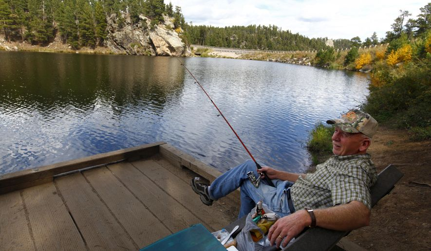 Dave Tucker fishes from a platform on Friday, Sept. 19, 2014 at Horsethief Lake near Mount Rushmore National Monument in South Dakota. The Black Hills National Forest Service will begin draining and dredging Horsethief Lake, as well as Bismarck Lake and Lakota Lake, to improve water quality. (AP Photo/Rapid City Journal)