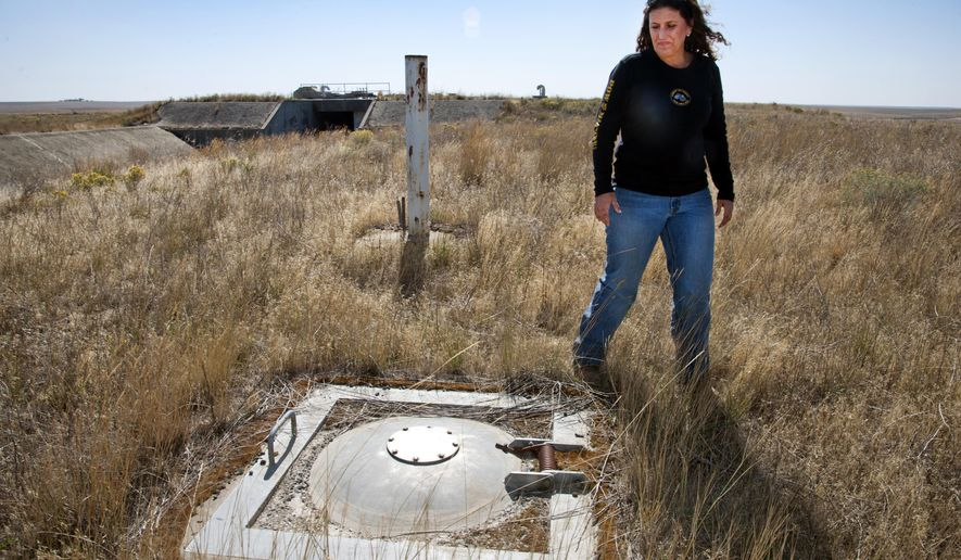 In a Sept. 12, 2014 photo, Teri Kramer points out an escape hatch over the living quarters of a former Atlas long-range ballistic missile site, one of nine underground Atlas sites in the eastern Washington, near Lamona, Wash., on the Kramer family's 20-acre site. The Kramers store farm equipment inside the facility, which was active from 1961 to 1965 as part of the U.S. Air Force's 567th Missile Squadron, assigned to Fairchild Air Force Base. (AP Photo/The Spokesman-Review, Dan Pelle)  COEUR D'ALENE PRESS OUT