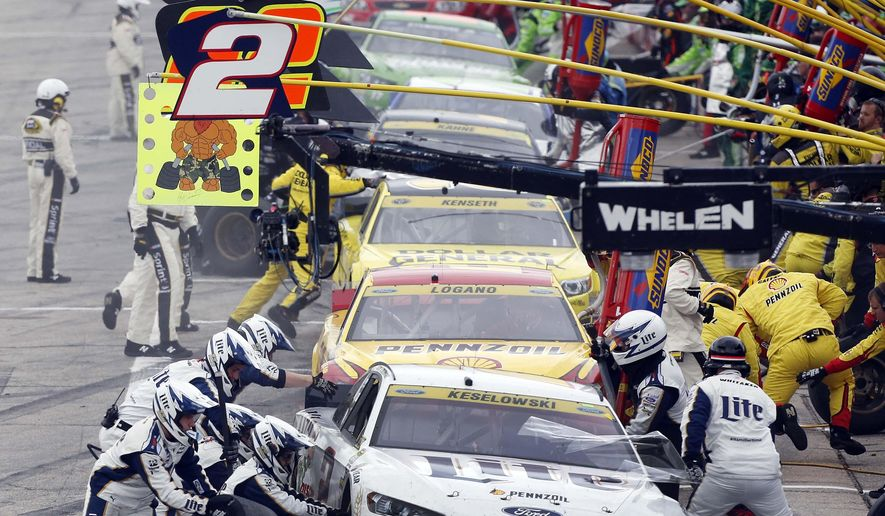 Brad Keselowski (2) leads cars in pit row during the NASCAR Sprint Cup series auto race at New Hampshire Motor Speedway, Sunday, Sept. 21, 2014, in Loudon, N.H. (AP Photo/Jim Cole)