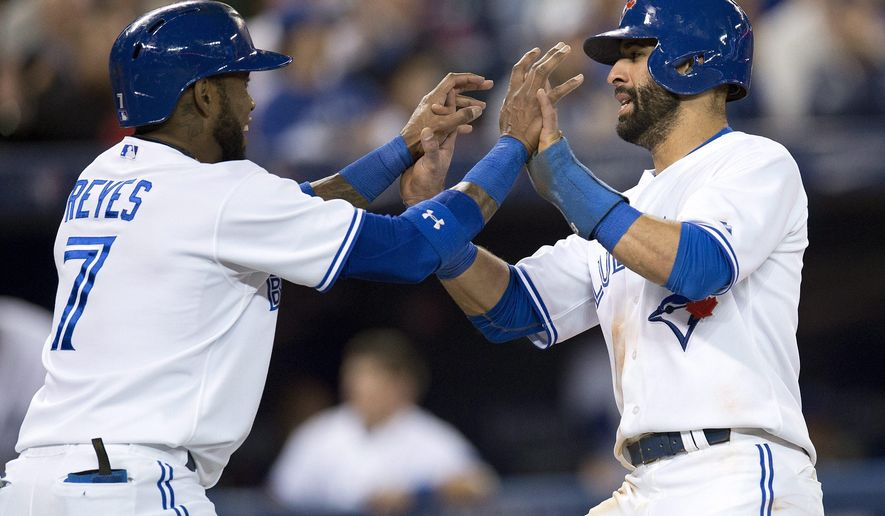 Toronto Blue Jays Jose Bautista, right, and Jose Reyes celebrate after scoring on a single by Edwin Encarnacion during the third inning of a baseball game, Monday, Sept. 22, 2014 in Toronto. (AP Photo/The Canadian Press, Frank Gunn)