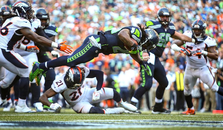 Seattle Seahawks' Marshawn Lynch flies into the end zone for a touchdown in overtime against the Denver Broncos in an NFL football game Sunday, Sept. 21, 2014, in Seattle. The Seahawks defeated the Broncos 26-20. (AP Photo/seattlepi.com, Joshua Trujillo)