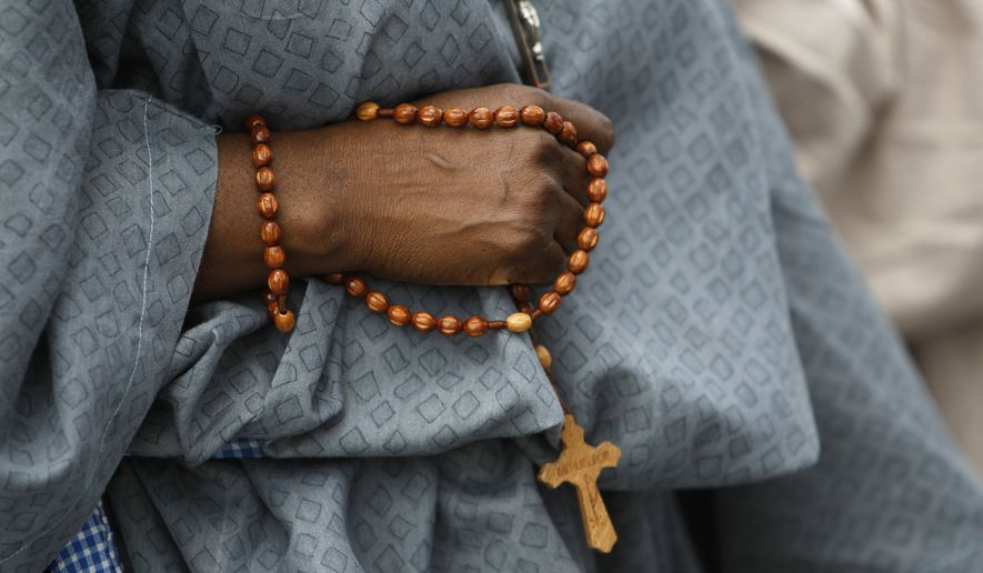 A parishioner from the Notre Dame d' Haiti Catholic Church carries a rosary as they walk the Stations of the Cross on Good Friday, Friday, April 6, 2012, in the Miami neighborhood of Little Haiti. (Associated Press) **FILE**