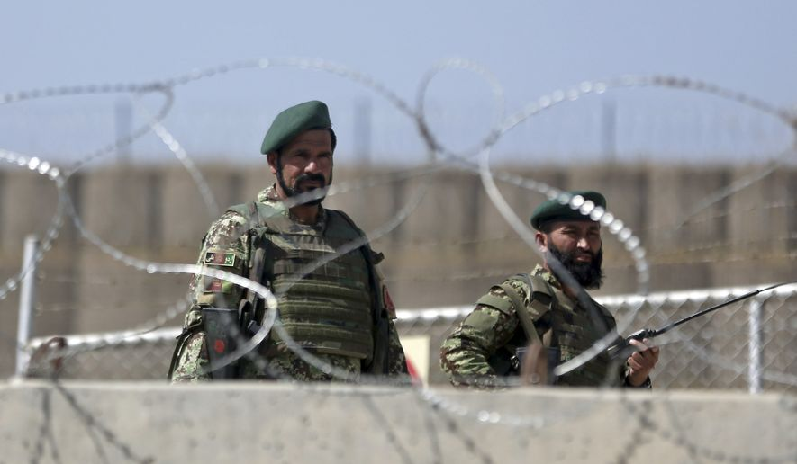 An Afghan laborer walks past a gate of Camp Qargha as Afghanistan National Army soldiers stand guard, west of Kabul, Afghanistan, Tuesday, Aug. 5, 2014. Earlier in the day, a man dressed in an Afghan army uniform opened fire on foreign troops at the military base, killing a U.S. two-star general and wounding others, among them a German brigadier general and a number of Americans troops, authorities said. (Associated Press) **FILE**