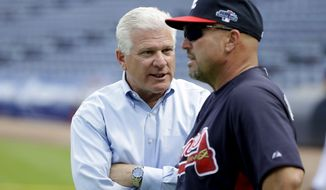 Atlanta Braves manager Fredi Gonzalez, right, talks with general manager Frank Wren during a baseball practice on Wednesday, Oct. 2, 2013, in Atlanta. The Los Angeles Dodgers are to play the Braves in Game 1 of the National League Division Series in Atlanta, Thursday. (AP Photo/David Goldman)
