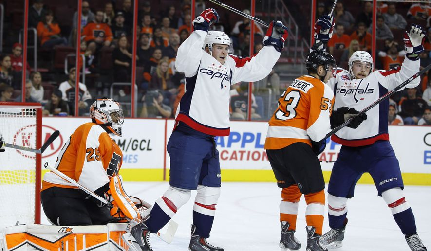 Washington Capitals' Liam O'Brien, right, and Garrett Mitchell celebrate past Philadelphia Flyers' Shayne Gostisbehere (53) and Ray Emery (29) after a goal by John Erskine during the first period of a preseason NHL hockey game, Monday, Sept. 22, 2014, in Philadelphia. (AP Photo/Matt Slocum)