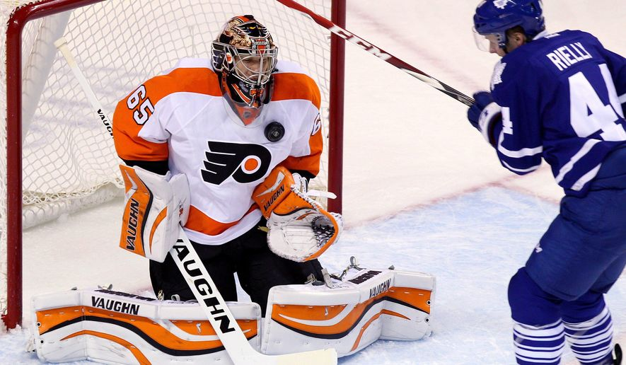 Toronto Maple Leafs Morgan Rielly of is blocked by Philadelphia Flyers goalie Anthony Stolarz during first period NHL pre-season action, Monday Sept. 22, 2014 in London, Ontario. (AP Photo/The Canadian Press, Dave Chidley)