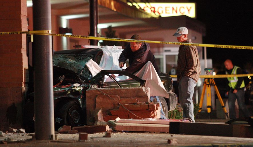Investigators examine the scene Sunday evening, Sept. 21, 2014 after two people were killed and a third left in critical condition when a car crashed into Wyoming Medical Center on Second Street in Casper, Wyo. Hospital spokeswoman Kristy Bleizeffer says the emergency room entrance was closed immediately after the crash but now has reopened. No hospital staff members were injured. (AP Photo/Casper Star-Tribune, Alan Rogers) MANDATORY CREDIT