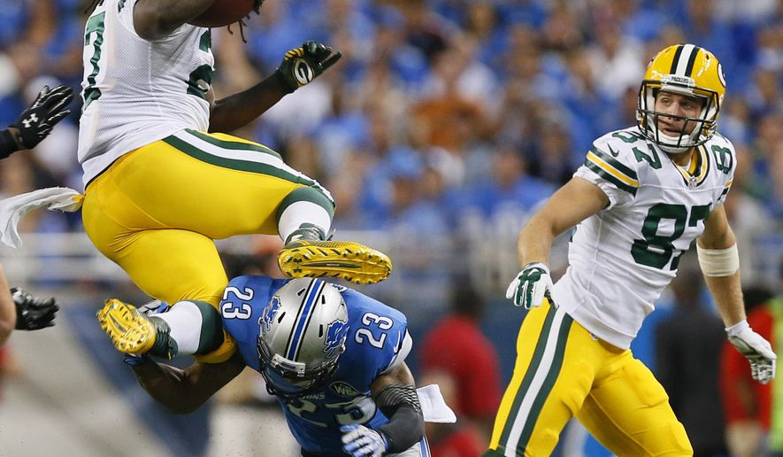 Detroit Lions cornerback Darius Slay (23) upends Green Bay Packers running back Eddie Lacy (27) during the first half of an NFL football game in Detroit, Sunday, Sept. 21, 2014. (AP Photo/Paul Sancya)