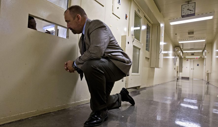 In this Sept. 16, 2014, photo, Dane County Sheriff David Mahoney talks to an inmate in an isolation cell at the jail in Madison, Wis. At the Dane County Jail, inmates with serious mental illnesses are routinely kept in similar cells for lack of an alternative. (AP Photo/Morry Gash)