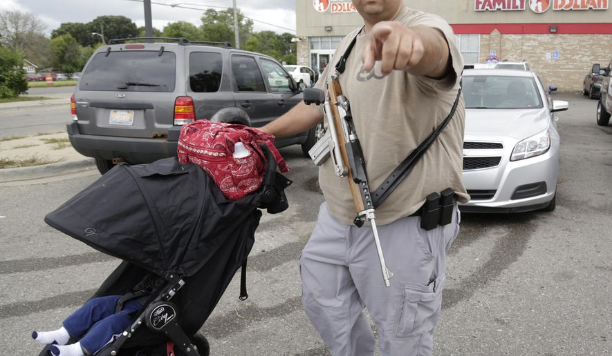 In this Sunday, Sept. 21, 2014 photo, gun-rights advocate Charles Copeland, 38, of Beverly Hills, Mich., pushes a stroller and carries his Ruger Mini 14 Rifle during a protest of the recent arrest of 24-year-old Elijah Woody, in Detroit. Woody says he was unlawfully arrested because police are against open-carry laws. (AP Photo/Detroit Free Press, Mandi Wright)  DETROIT NEWS OUT;  NO SALES