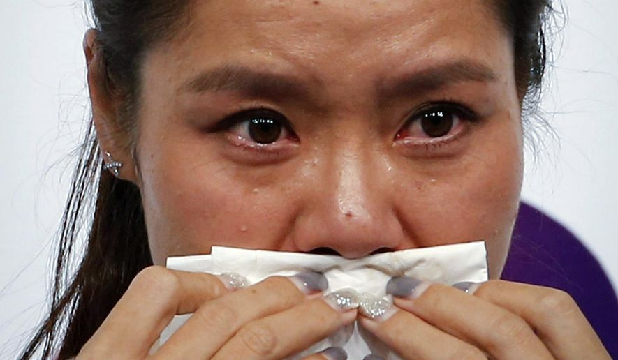 In this photo taken Sunday, Sept. 21, 2014, Chinese tennis player Li Na wipes her tears during a press conference to announce her retirement in Beijing. The two-time Grand Slam champion from China who took tennis in Asia to a new level, has retired due to recurring knee injuries. (AP Photo/Vincent Thian)