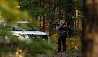 A Pennsylvania State Trooper draw's his weapon in a wooded area on Snow Hill Road in Price Township, Pa., during a massive manhunt for suspected killer Eric Frein on Sunday, Sept. 21, 2014, near Canadensis, Pa.  (AP Photo / The Scranton Times-Tribune, Butch Comegys)